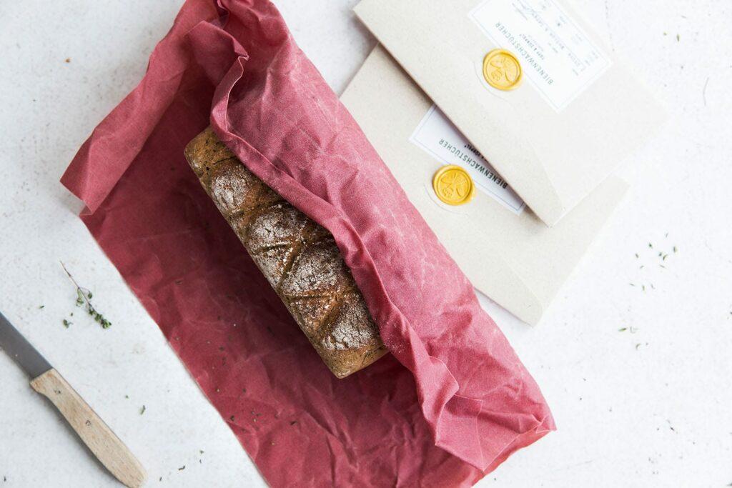 Ein Brot eingepackt in einem roten Bienenwachstuch, daneben liegen zwei Produktverpackungen.