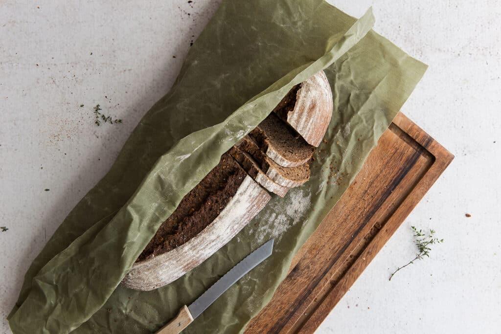 Ein angeschnittenes Brot in einem Bienenwachstuch in Grün liegt auf einem Holzbrett.