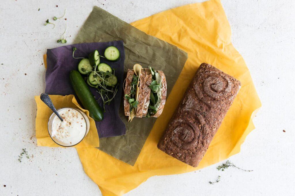 Ein Glas gefüllt mit Joghurt, eine Gurke und eine Schnitte sowie ein Brot liegen auf Bienenwachstücher in den Farben Gelb, Lila und Grün.