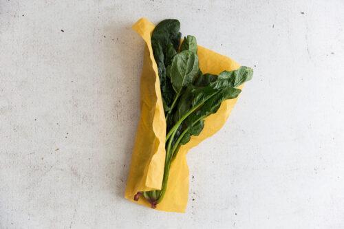 Blattspinat eingepackt im Bienenwachstuch in der Farbe Gelb.