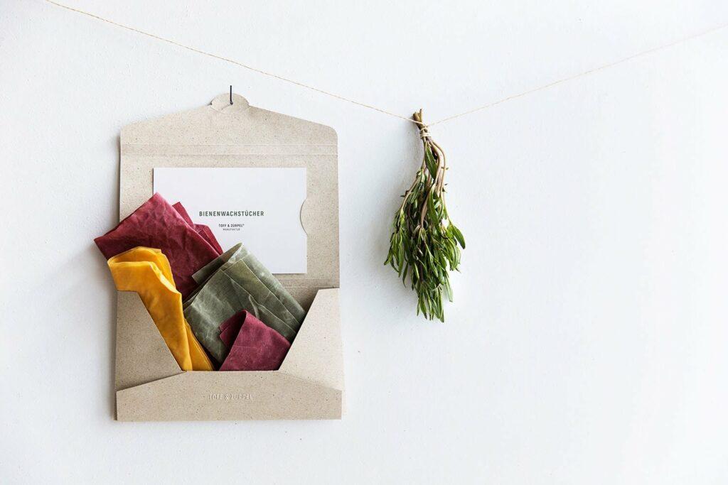 Unsere wiederverwendbare Graspapier-Verpackung offen aufgehängt und gefüllt mit Bienenwachstücher in den Farben Grün, Rot und Gelb, daneben hängt ein Bündel Kräuter.