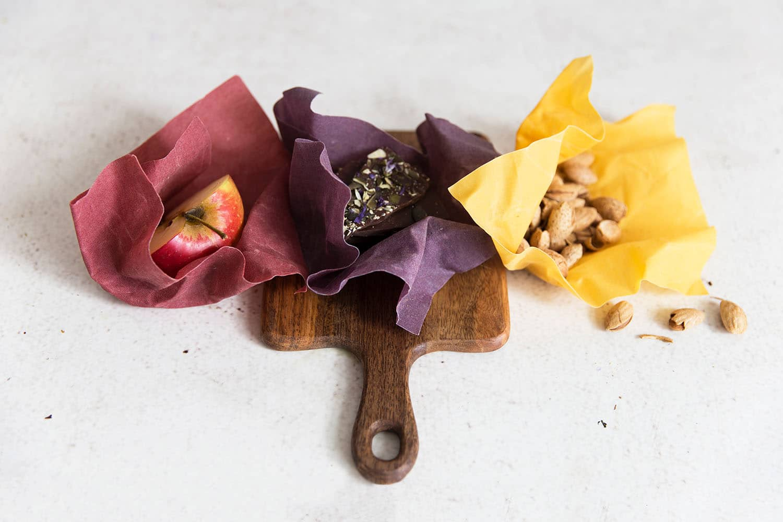 Drei Bienenwachstücher in den Farben Rot, Lila und Gelb liegen auf einem Brett und umhüllen Nüsse, ein Stück von einem Apfel und einer Schokolade.