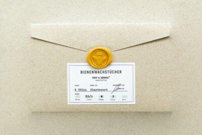 Die Verpackung aus Graspapier mit einem Bienen-Siegelstempel für das Bienenwachstücher Starterset in Gelb, Grün & Lila.
