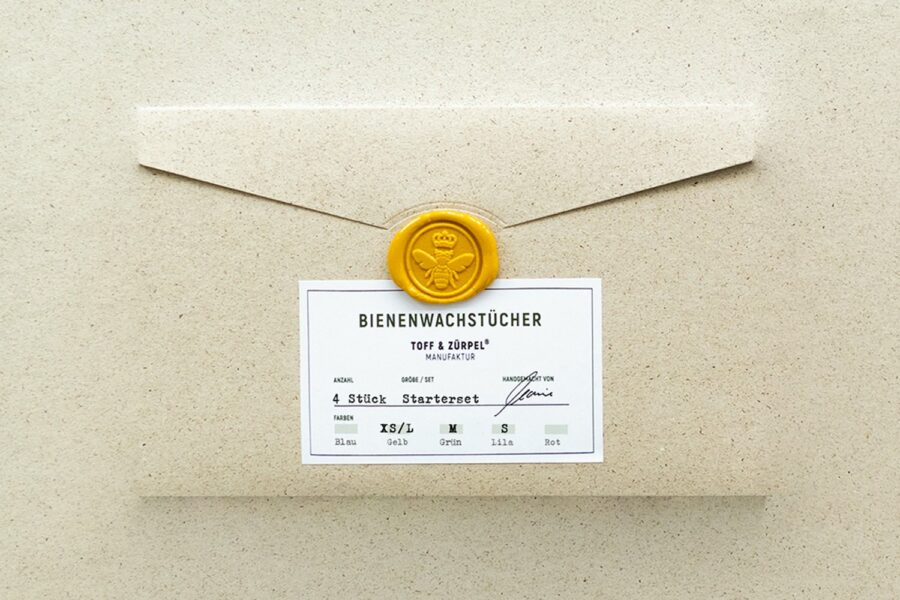 The packaging made of grass paper with a bee seal stamp for the beeswax starter set in yellow, green & purple.