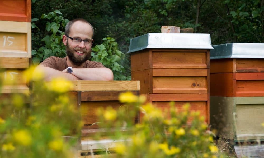 Demeter-Imker Alexander Schlotter lehnt auf einem Bienenstock