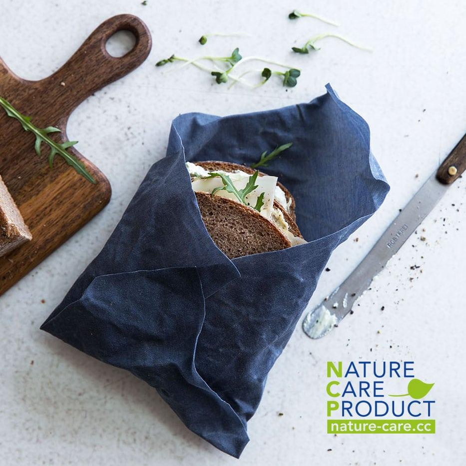 """Ein Käsebrot eingepackt in einem blauen Bienenwachstuch - daneben ist das Logo von dem Zertifikat """"Nature Care Product"""" abgebildet"""